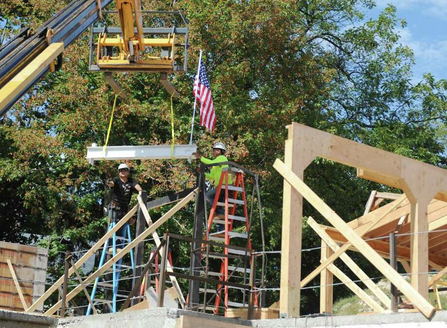 The final beam is lifted into place during the Topping Off Ceremony and Barbecue at the Greenwich Historical Society in the Cos Cob section of Greenwich, Conn. Wednesday, Sept. 27, 2017. Local officials and donors signed the final beam of the expansion and renovation project before it was lifted into place. Photo: Tyler Sizemore / Hearst Connecticut Media / Greenwich Time