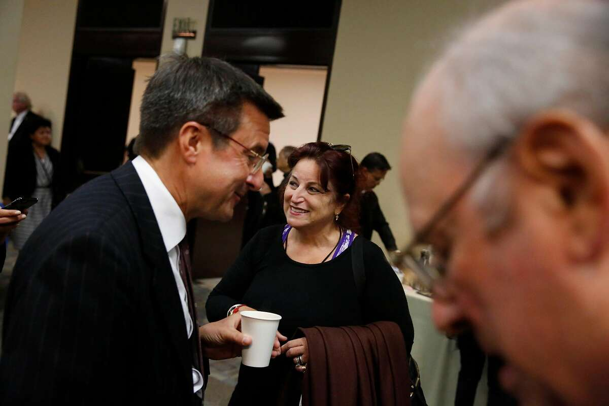 Michael Pappas (left), Executive Director of the San Francisco Interfaith Council, and Angela Alioto talk at a reception after the funeral mass of Archbishop Quinn at the Cathedral of Saint Mary of the Assumption on July 10, 2017 in San Francisco.