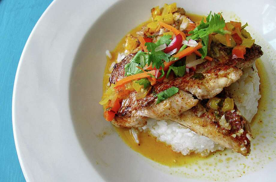 Crispy snapper in coconut sauce with rice at Ocho. Photo: Mike Sutter /San Antonio Express-News