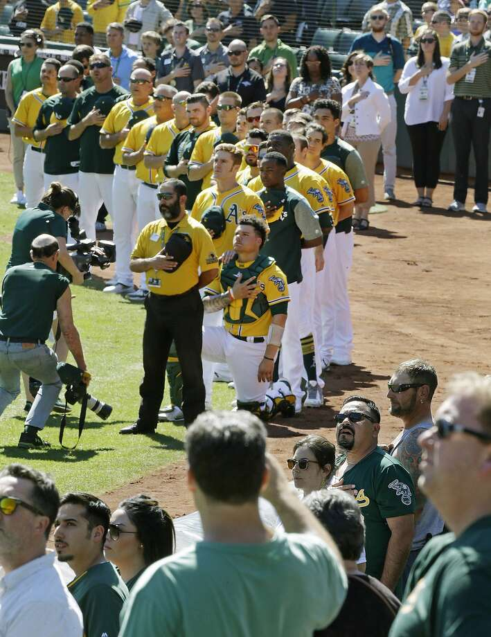 Oakland Athletics fans stand during the national anthem as Athletics catcher Bruce Maxwell kneels for the fifth consecutive day prior to the baseball game against the Seattle Mariners on Wednesday, Sept. 27, 2017, in Oakland, Calif. (AP Photo/Ben Margot) Photo: Ben Margot, Associated Press