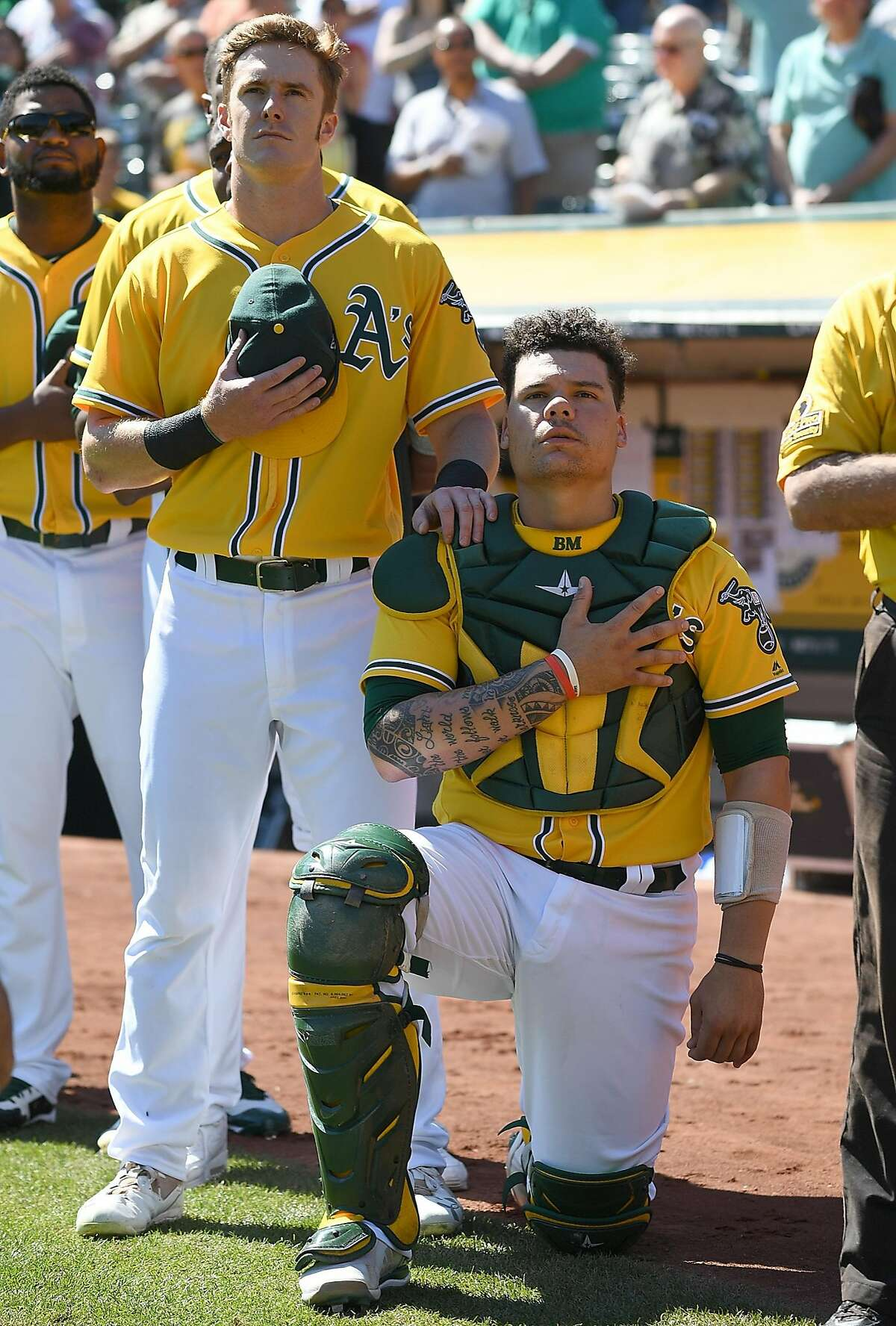 OAKLAND, CA - SEPTEMBER 27: Bruce Maxwell #13 of the Oakland Athletics kneels in protest next to teammate Mark Canha #20 duing the singing of the National Anthem prior to the start of the game against the Seattle Mariners at Oakland Alameda Coliseum on September 27, 2017 in Oakland, California. (Photo by Thearon W. Henderson/Getty Images)