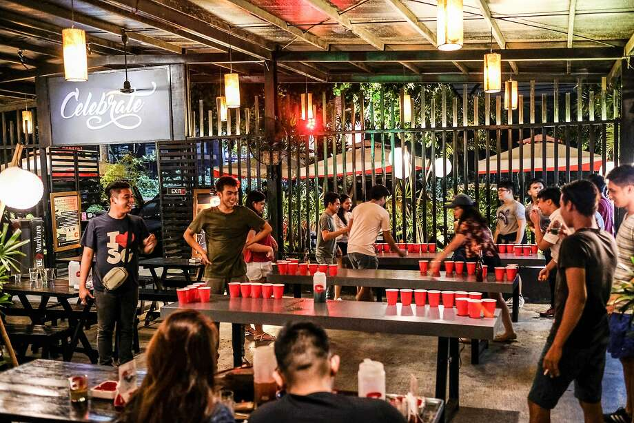Regular patrons and BPO employees enjoy a game of beer pong in Central BBQ in Quezon City. Photo: Veejay Villafranca, Veejay Villafranca For The San Francisco Chronicle