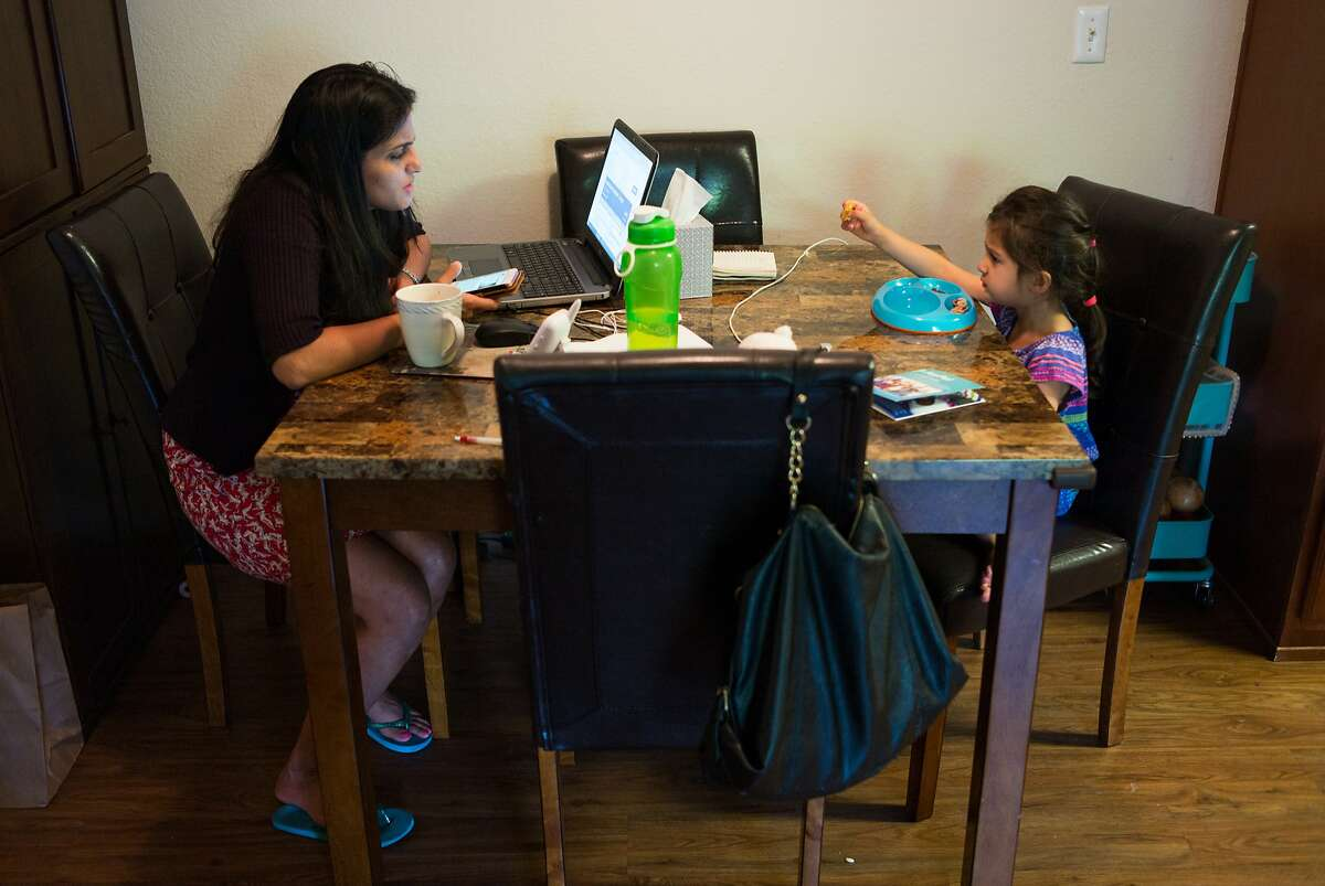 Karishma Chawla listens to her daughter a Naisha as she works at her home in San Jose, Calif. on Friday, Aug. 18, 2017. For decades spouses of H-1B visa holders could not work, until two years ago when President Obama issued a work authorization. But now his authorization is under threat by the Trump administration who is trying to rid these visa holders from the ability to work.