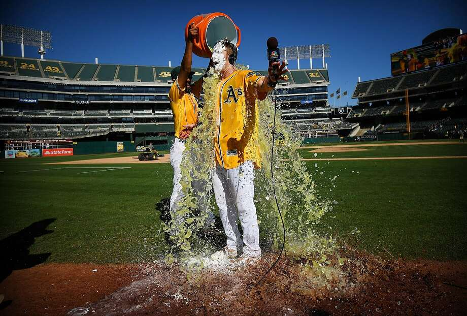 OAKLAND, CA - SEPTEMBER 27:  Mark Canha #20 of the Oakland Athletics is showered with Gatorade by teammate Marcus Semien #10 after Canha hit a walk-off solo home run to defeat the Seattle Mariners 6-5 at Oakland Alameda Coliseum on September 27, 2017 in Oakland, California.  (Photo by Thearon W. Henderson/Getty Images) Photo: Thearon W. Henderson, Getty Images