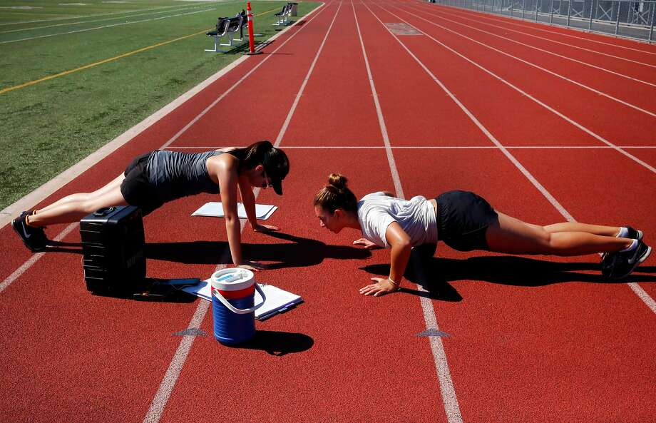 Assistant drum major Lizzy Mirov (left) and co-head drum major Shani Zuniga, both 16, do pushups during rehearsal. Photo: Leah Millis, The Chronicle