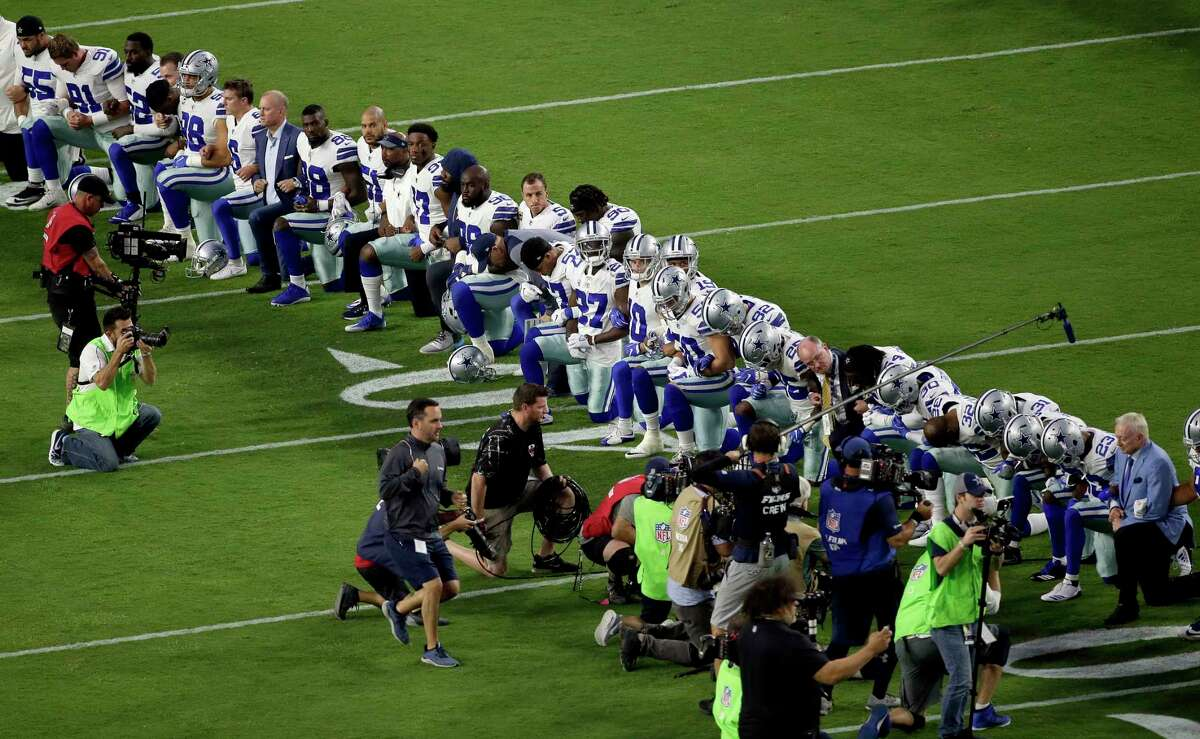 The Dallas Cowboys, with owner Jerry Jones, far right, take a knee prior to the national anthem this week.