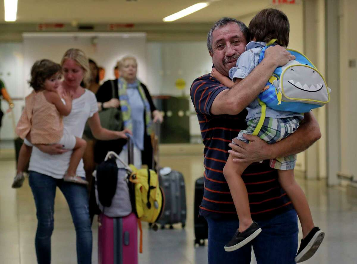 Juan Rojas, right, of Queens, hugs his 4-year-old grandson Elias Rojas, as his daughter-in-law Cori Rojas, left, carries her daughter Lilly, 3, through the terminal at JFK airport after Cori arrived on a flight from San Juan, Puerto Rico, Tuesday, Sept. 26, 2017, in New York. Cori Rojas, who is a school teacher in Puerto Rico, fled Puerto Rico with her children after Hurricane Maria left the island devastated and will stay with her in-laws in Queens while her husband, who works for a global insurance firm chose to stay behind. (AP Photo/Julie Jacobson) ORG XMIT: NYJJ101