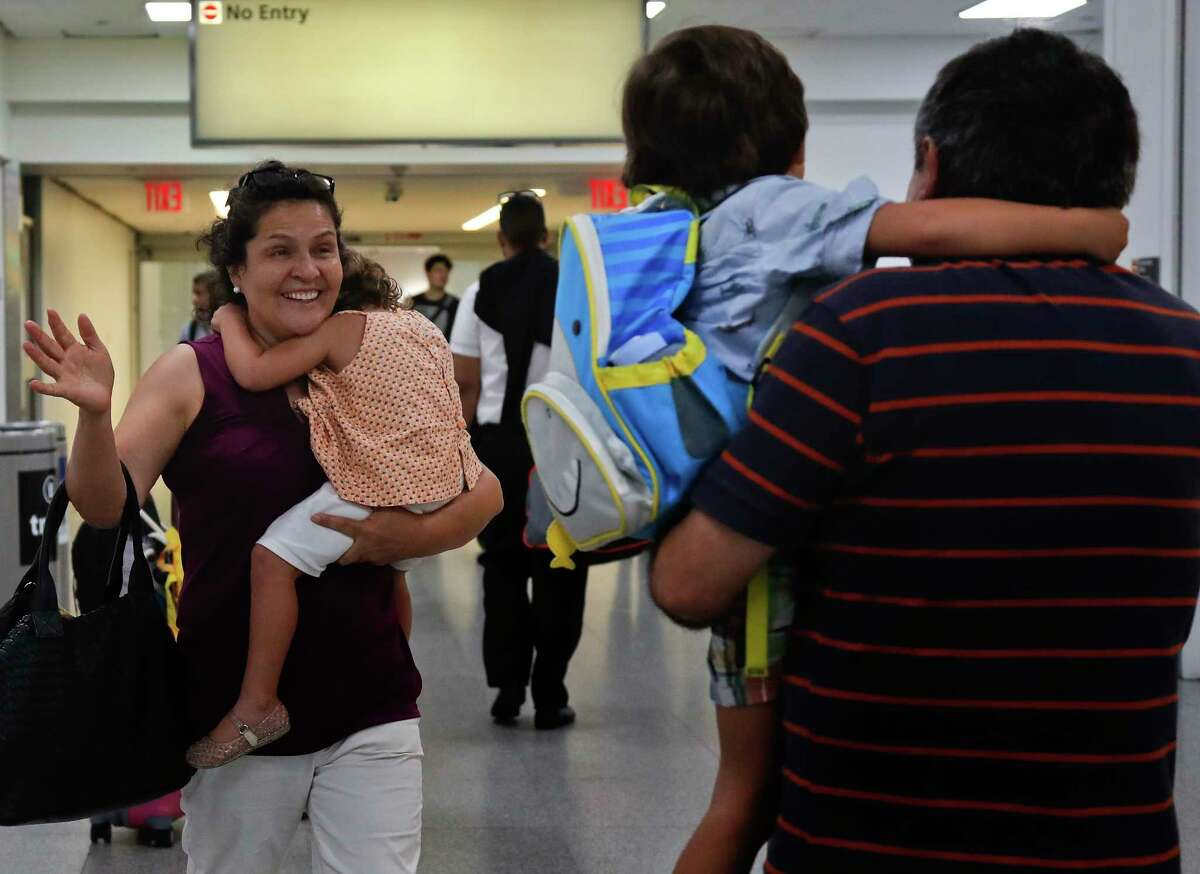 Elena Rojas, left, of Queens, N.Y. reacts as she greets her 4-year-old grandson Elias, center, while carrying her 3-year-old granddaughter Lilly after the children arrived at JFK airport from Puerto Rico with their mother Cori Rojas (not pictured), Tuesday, Sept. 26, 2017 in New York. Cori Rojas and her children fled Puerto Rico after Hurricane Maria devastated the island and will stay with her in-laws in Queens. (AP Photo/Julie Jacobson) ORG XMIT: NYJJ103