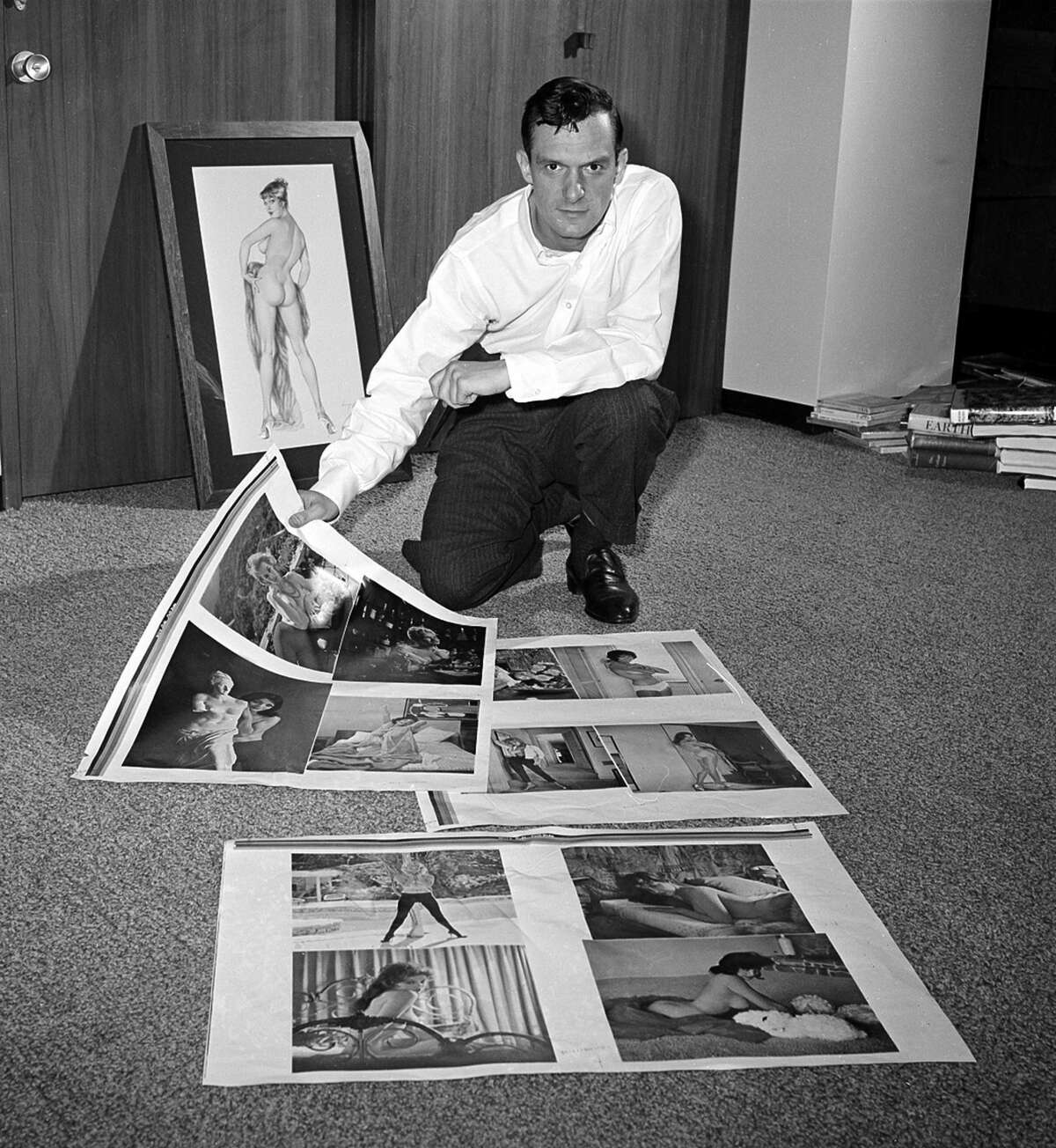 Publisher Hugh Hefner looks over proof sheets for his magazine Playboy, in Chicago, on June 20, 1961.
