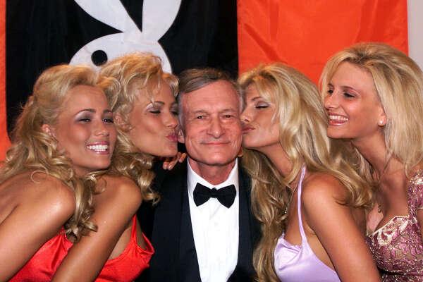 En esta foto del 14 de mayo de 1999, el fundador y editor en jefe de Playboy Hugh Hefner recibe besos de conejitas de Playboy en el Festival de Cine de Cannes, en Cannes, Francia. Hefner murió el miércoles 27 de septiembre del 2017 de causas naturales. Tenía 91 años. (AP Foto/Laurent Rebours, Archivo)