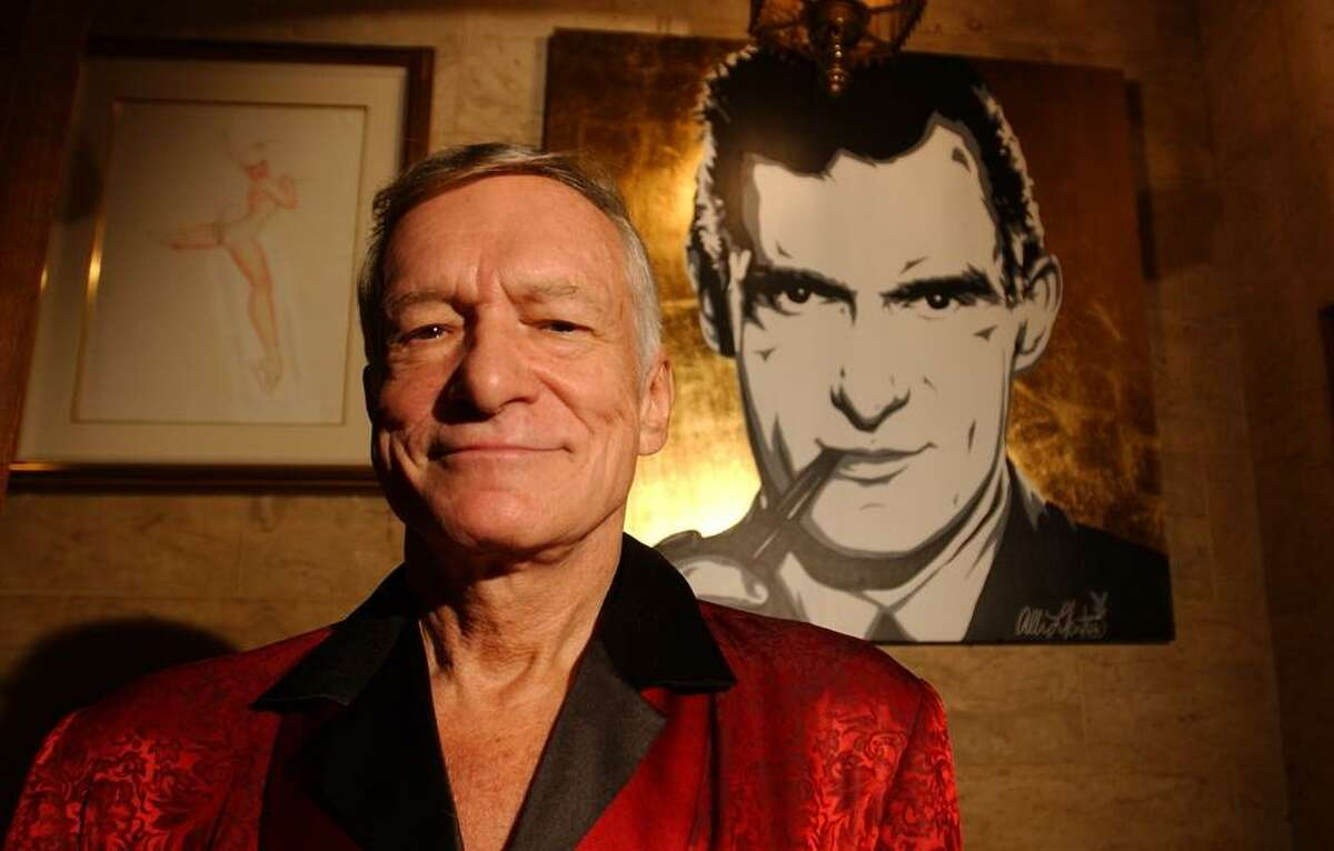 Hefner, the pipe-smoking hedonist garbed in his telltale silk pajamas, poses in 2003, 50 years after Playboy's first issue.
