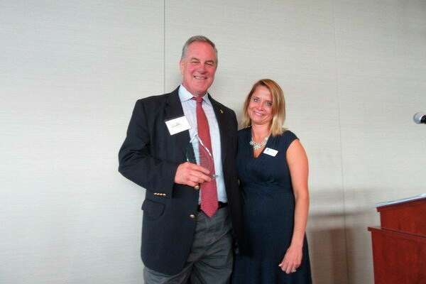 Doug Brown, ASTI Environmental's director of development, ireceives the Sieghart Award by Jennifer Owens, president of Lakeshore Advantage. (Photo provided)