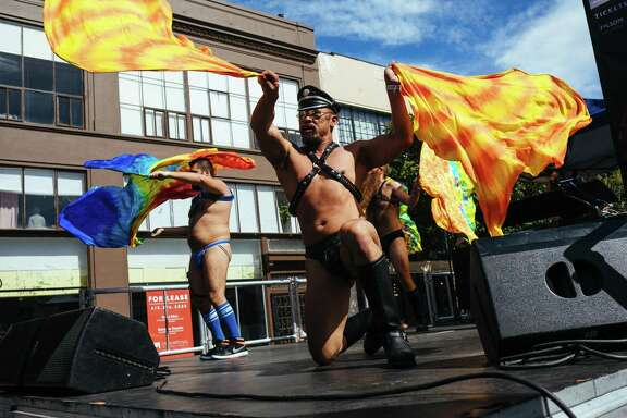 Performers wave flags on stage at the Folsom Street Fair in San Francisco on Sunday, September 24, 2017.