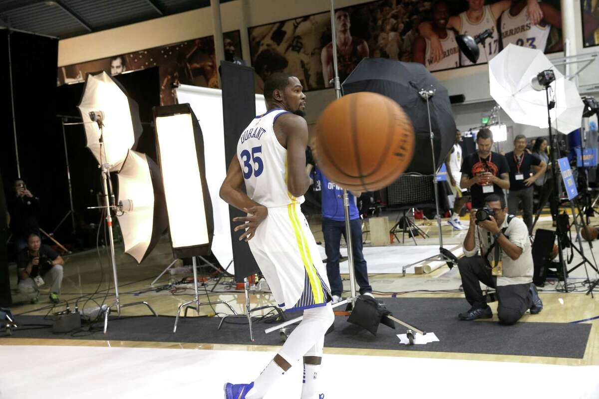 Warriors' Kevin Durant goes behind the back with the basketbeall during a portrait sessoin at the 2017 Golden State Warriros Media Day in Oakland on Friday, September 22, 2017.
