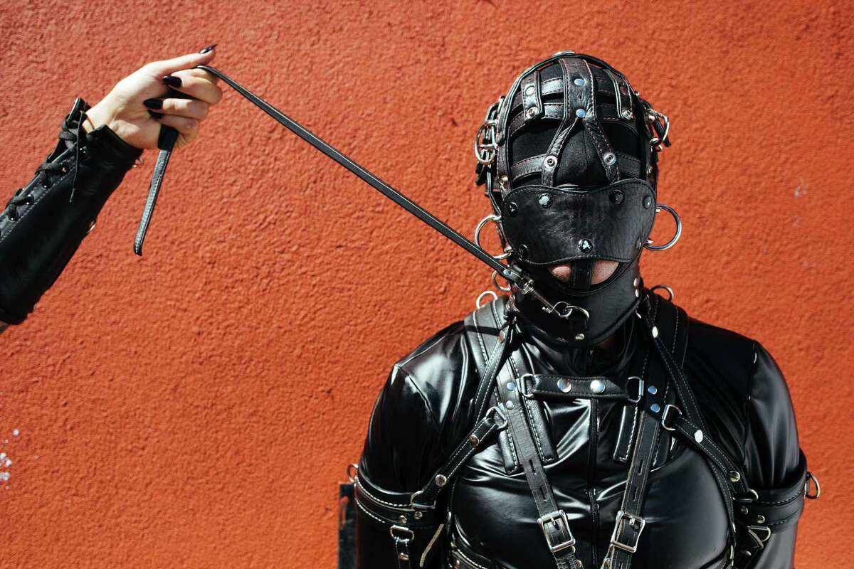 Marie Champagne, left, holds Jason Basciano on a leash during the Folsom Street Fair in San Francisco on Sunday, September 24, 2017.