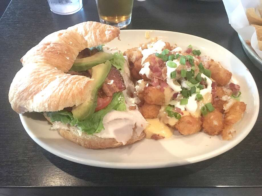 Pictured is the turkey avocado club and loaded tater tots at 99 Hops House inside Hollywood Casino in Maryland Heights. Photo: Bill Roseberry