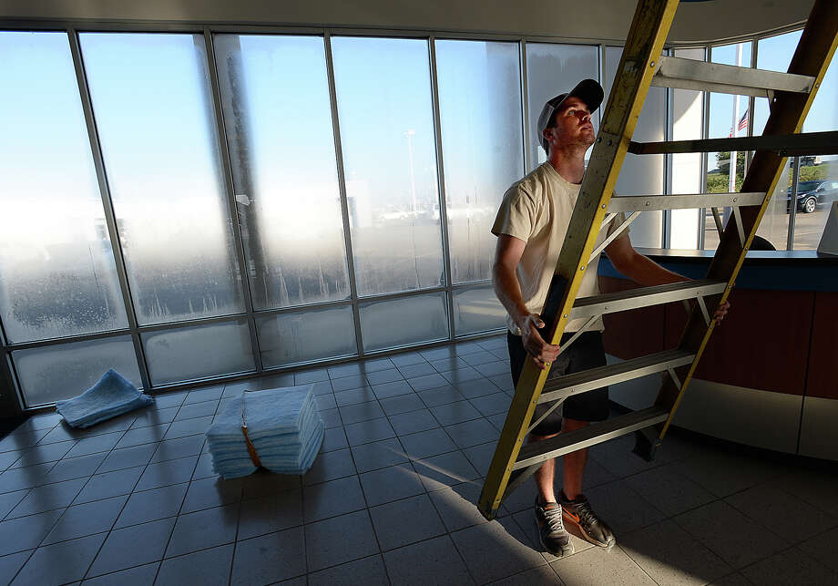 Jeremy Tubbs with A1 Filters climbs up to replace air filters at the Twin City car dealerships in Nederland Tuesday. The business was out of work for three weeks due to clients being closed during Tropical Storm Harvey.   Photo taken Tuesday, September 26, 2017 Kim Brent/The Enterprise Photo: Kim Brent / BEN