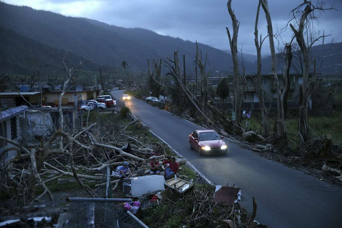 Neighbors sit on a couch outside their destroyed homes as sun sets in the aftermath of Hurricane Maria, in Yabucoa, Puerto Rico, Tuesday, Sept. 26, 2017. Governor Ricardo Rossello and Resident Commissioner Jennifer Gonzalez, the island's representative in Congress, have said they intend to seek more than a billion in federal assistance and they have praised the response to the disaster by President Donald Trump, who plans to visit Puerto Rico next week, as well as FEMA Administrator Brock Long. (AP Photo/Gerald Herbert)