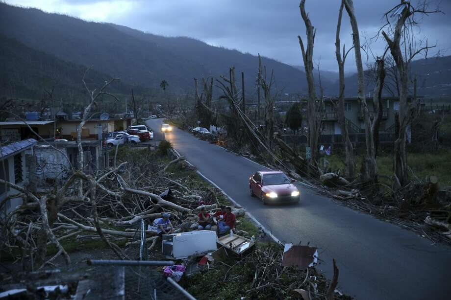 Neighbors sit on a couch outside their destroyed homes as sun sets in the aftermath of Hurricane Maria, in Yabucoa, Puerto Rico, Tuesday, Sept. 26, 2017. Governor Ricardo Rossello and Resident Commissioner Jennifer Gonzalez, the island's representative in Congress, have said they intend to seek more than a billion in federal assistance and they have praised the response to the disaster by President Donald Trump, who plans to visit Puerto Rico next week, as well as FEMA Administrator Brock Long.  (AP Photo/Gerald Herbert) Photo: Gerald Herbert/AP