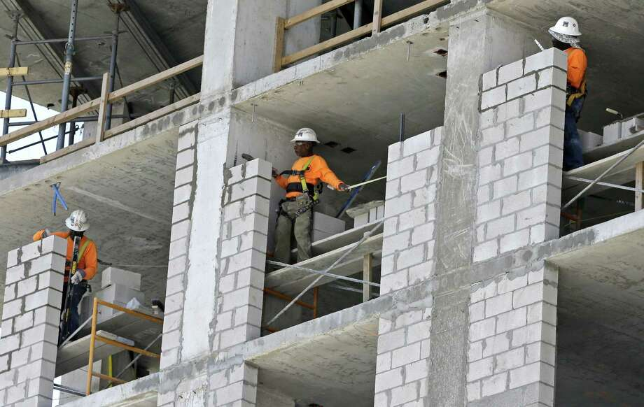 Construction workers work on an apartment high rise in Miami in May. The April-June expansion in the gross domestic product is up slightly from a 3 percent estimate made a month ago, the Commerce Department reported Thursday. Photo: Alan Diaz /Associated Press / Copyright 2017 The Associated Press. All rights reserved.