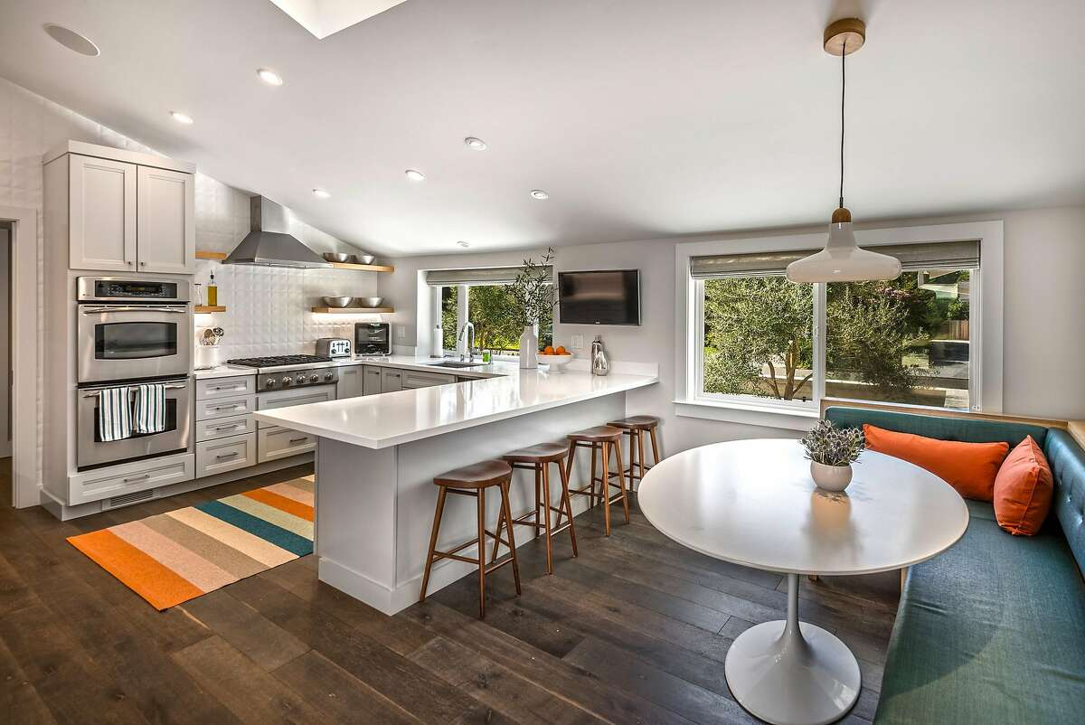 The kitchen includes dual ovens, display shelving, and a breakfast bar.