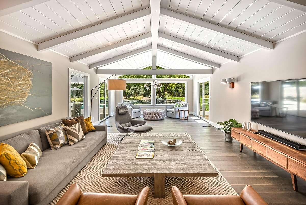 The living room boasts a vaulted, beamed ceiling and large picture windows.