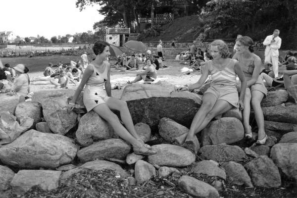 Three women perch on the rocks while enjoying an afternoon at the Shorewood Beach Club in Stamford, Connecticut, circa 1930.