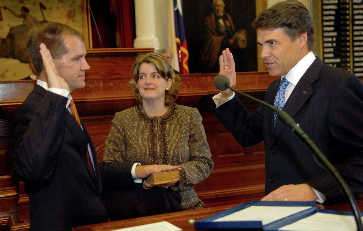 Don Willett, left, is sworn in to the state Supreme Court by Gov. Rick Perry, right, as Tiffany Willett, center, Don Willett's wife, holds the Bible at the State Capitol in Austin, Texas, on Monday, Nov. 21, 2005. (AP Photo/Austin American-Statesman, Rodolfo Gonzalez)
