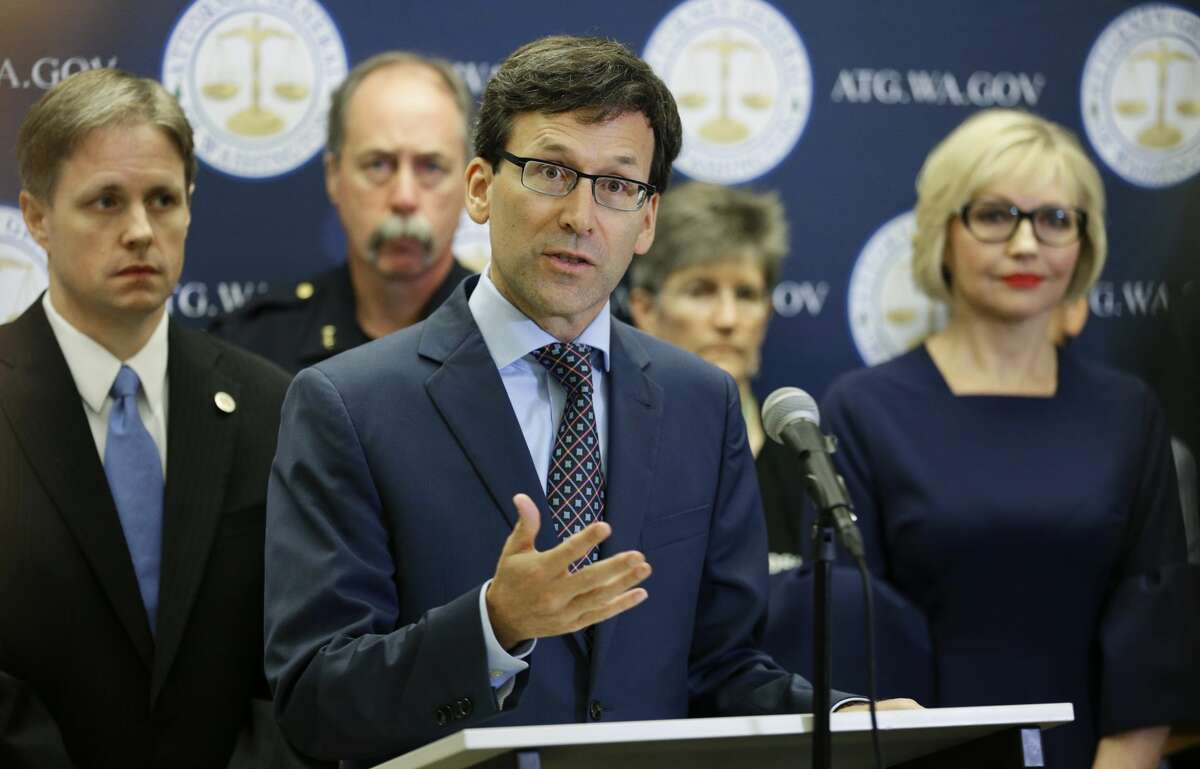 Washington Attorney General Bob Ferguson, center, talks to reporters Thursday, Sept. 28, 2017, in Seattle, after announcing that the state and the city of Seattle are filing lawsuits against several makers of opioids, including Purdue Pharma, seeking to recoup costs incurred by government when the drugs, which many officials blame for a national addiction crisis, are abused. (AP Photo/Ted S. Warren)