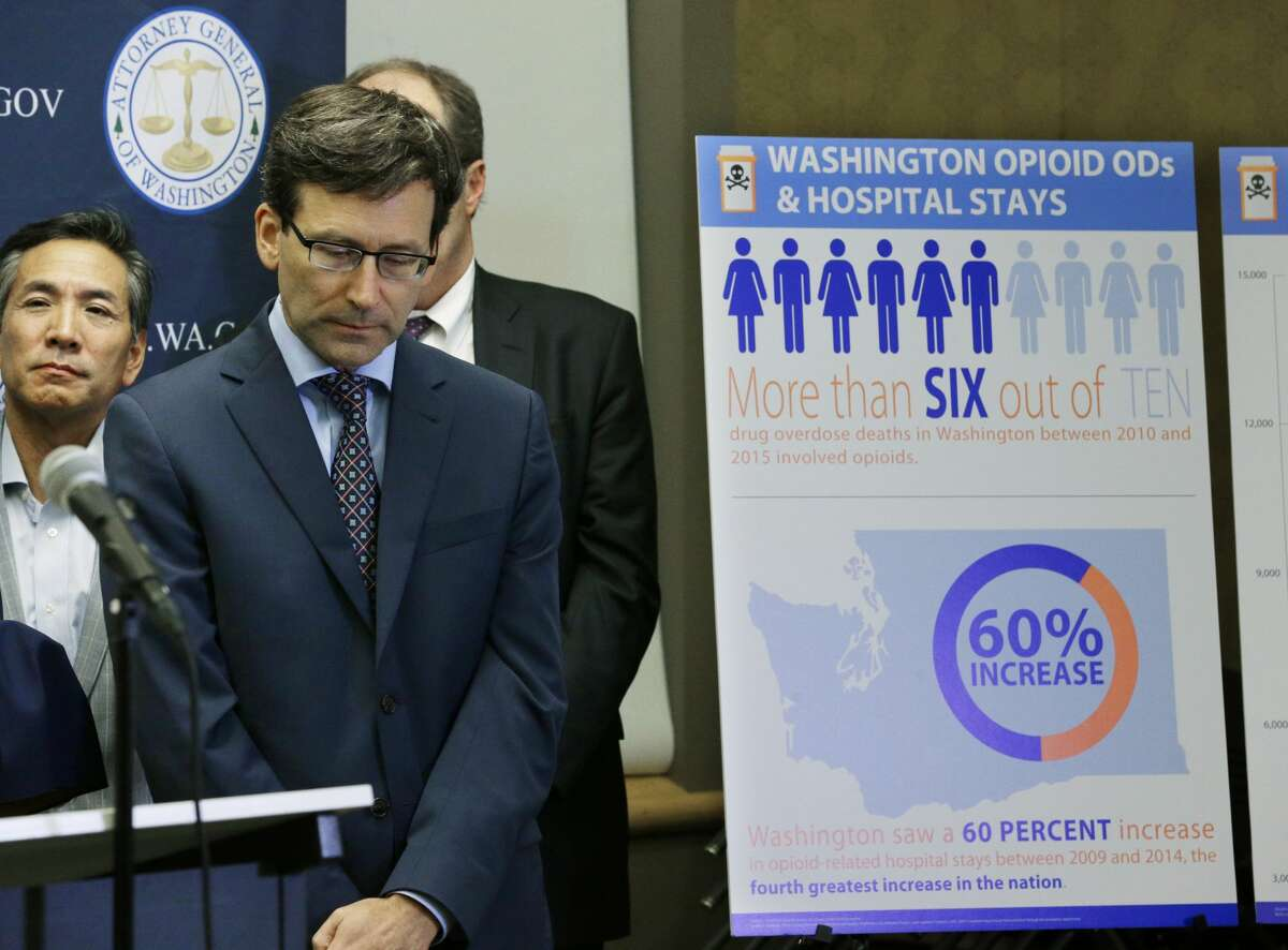 Washington Attorney General Bob Ferguson, second from left, listens to a question, Thursday, Sept. 28, 2017, in Seattle, as he stands near a chart detailing increases in overdoses and hospital stays relating to opioid use in Washington state. (AP Photo/Ted S. Warren)