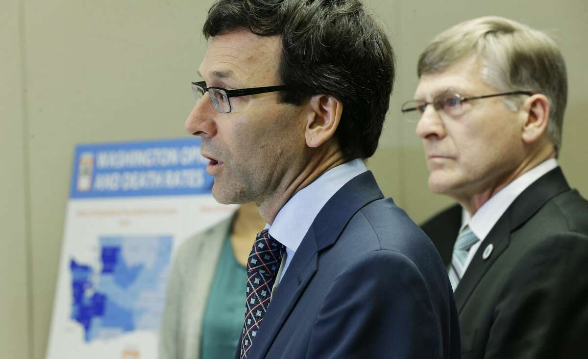 Washington Attorney General Bob Ferguson, center, talks to reporters Thursday, Sept. 28, 2017, in Seattle, as Seattle City Attorney Pete Holmes, right, looks on. Ferguson said Thursday that the state and the city of Seattle are filing lawsuits against several makers of opioids, including Purdue Pharma, seeking to recoup costs incurred by government when the drugs -- which many officials blame for a national addiction crisis -- are abused. (AP Photo/Ted S. Warren)