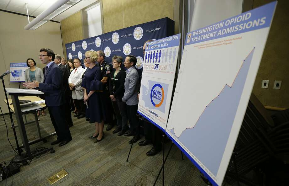 Washington Attorney General Bob Ferguson, second from left, talks to reporters Thursday, Sept. 28, 2017, in Seattle, as he stands near a chart detailing the increase of admissions for opioid addiction treatment in Washington state. Ferguson said Thursday that the state and the city of Seattle are filing lawsuits against several makers of opioids, including Purdue Pharma, seeking to recoup costs incurred by government when the drugs, which many officials blame for a national addiction crisis, are abused. (AP Photo/Ted S. Warren) Photo: Ted S. Warren/AP