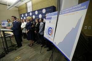Washington Attorney General Bob Ferguson, second from left, talks to reporters Thursday, Sept. 28, 2017, in Seattle, as he stands near a chart detailing the increase of admissions for opioid addiction treatment in Washington state. Ferguson said Thursday that the state and the city of Seattle are filing lawsuits against several makers of opioids, including Purdue Pharma, seeking to recoup costs incurred by government when the drugs, which many officials blame for a national addiction crisis, are abused. (AP Photo/Ted S. Warren)