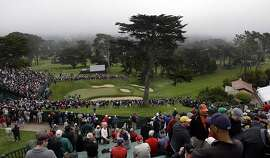Fan watch a group on the 18th green during a practice round for the U.S. Open Championship golf tournament Wednesday, June 13, 2012, at The Olympic Club in San Francisco. (AP Photo/Charlie Riedel)