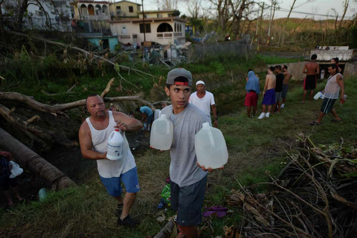 People carry water in bottles retrieved from a canal due to lack of water following passage of Hurricane Maria, in Toa Alta, Puerto Rico, on September 25, 2017. The US island territory, working without electricity, is struggling to dig out and clean up from its disastrous brush with the hurricane, blamed for at least 33 deaths across the Caribbean. / AFP PHOTO / HECTOR RETAMALHECTOR RETAMAL/AFP/Getty Images ORG XMIT: Hurricane