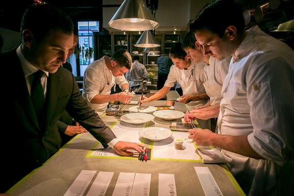 The team of cooks work plating dishes at Saison in San Francsico, Calif., on Wednesday, May 14th, 2014.