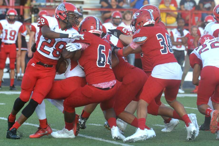 The Plainview defense, including D'Shae Casias, 64, and Charlie Rodriguez, 30, team up to stop a Borger running back last week. The Bulldogs will begin District 3-5A play Friday when they host Palo Duro in a 7 p.m. start. Photo: Skip Leon/Plainview Herald