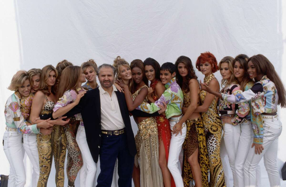 Gianni Versace poses with a group of models wearing his spring-summer collection in Milan, March 1991. (Photo by Vittoriano Rastelli/CORBIS/Corbis via Getty Images)