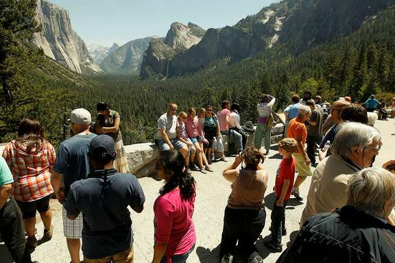Park visitors gather at Tunnel View observation point, at Yosemite National Park, on Saturday May 12, 2012. Visitors to California national parks may notice more trash on trails, longer lines at service booths and fewer rangers this summer as the pinch of the federal government's budget problems grow increasingly difficult to overlook.