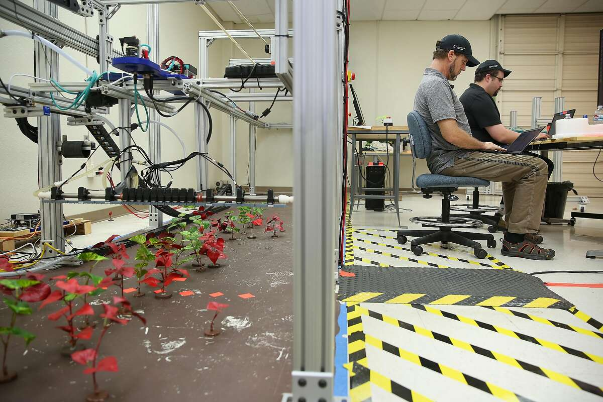 Principle software engineer Kurt Ottaway (front right) and senior software engineer Zeb Wheeler (right) work on development of the rail gun platform at Blue River labs. They test with the machine with sprayers, at left, which distinguish between weeds and regular plantings. John Deere recently bought machine learning company Blue River Technology.