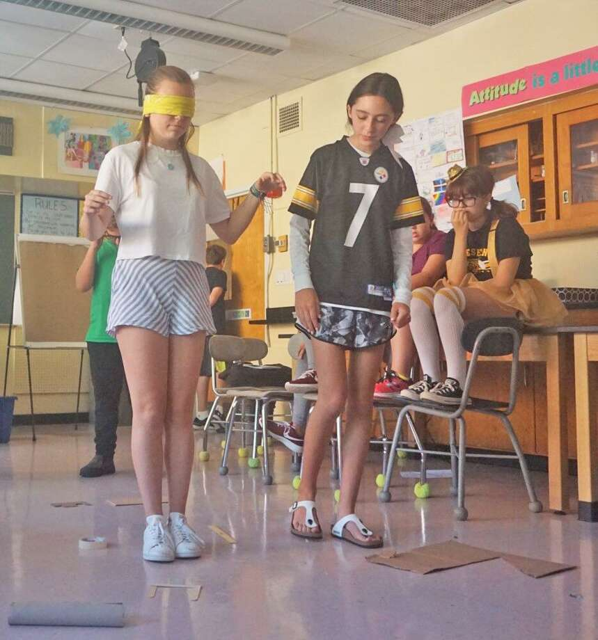 """Eighth grader Erin Morlock (L) is guided through a """"mine field"""" on the classroom floor by her classmate Mary Kanos (R) on Sept. 27 as part of a morning of social and emotional learning activities at Western Middle School. Photo: Emilie Munson"""