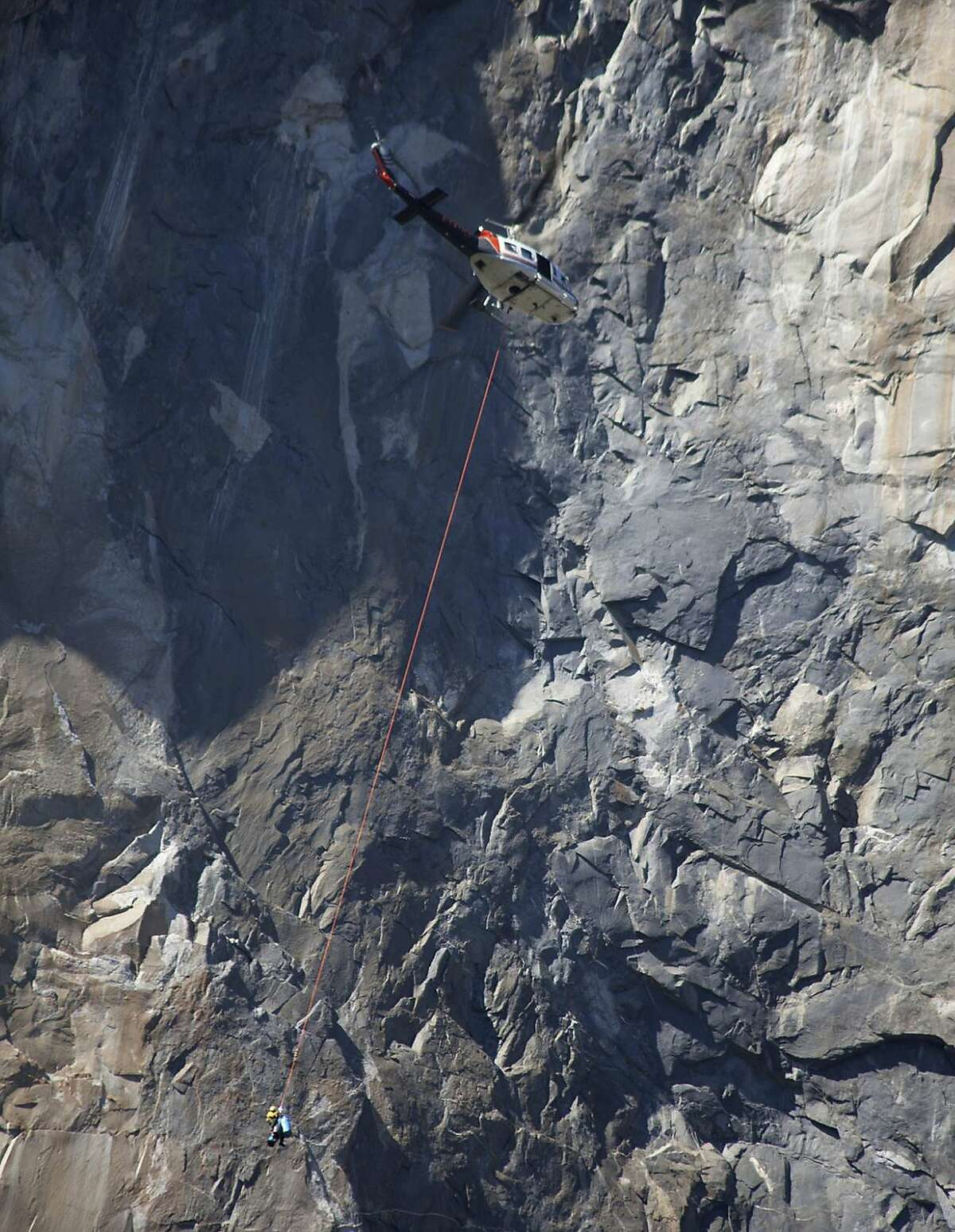 In this Wednesday Sept. 27, 2017, photo provided by Dakota Snider, photographer and Yosemite resident, a helicopter makes a rescue off El Capitan after a major rock fall in Yosemite National Park, Calif. All areas in California's Yosemite Valley are open Thursday, a day after the fatal rock fall. (Dakota Snider via AP)