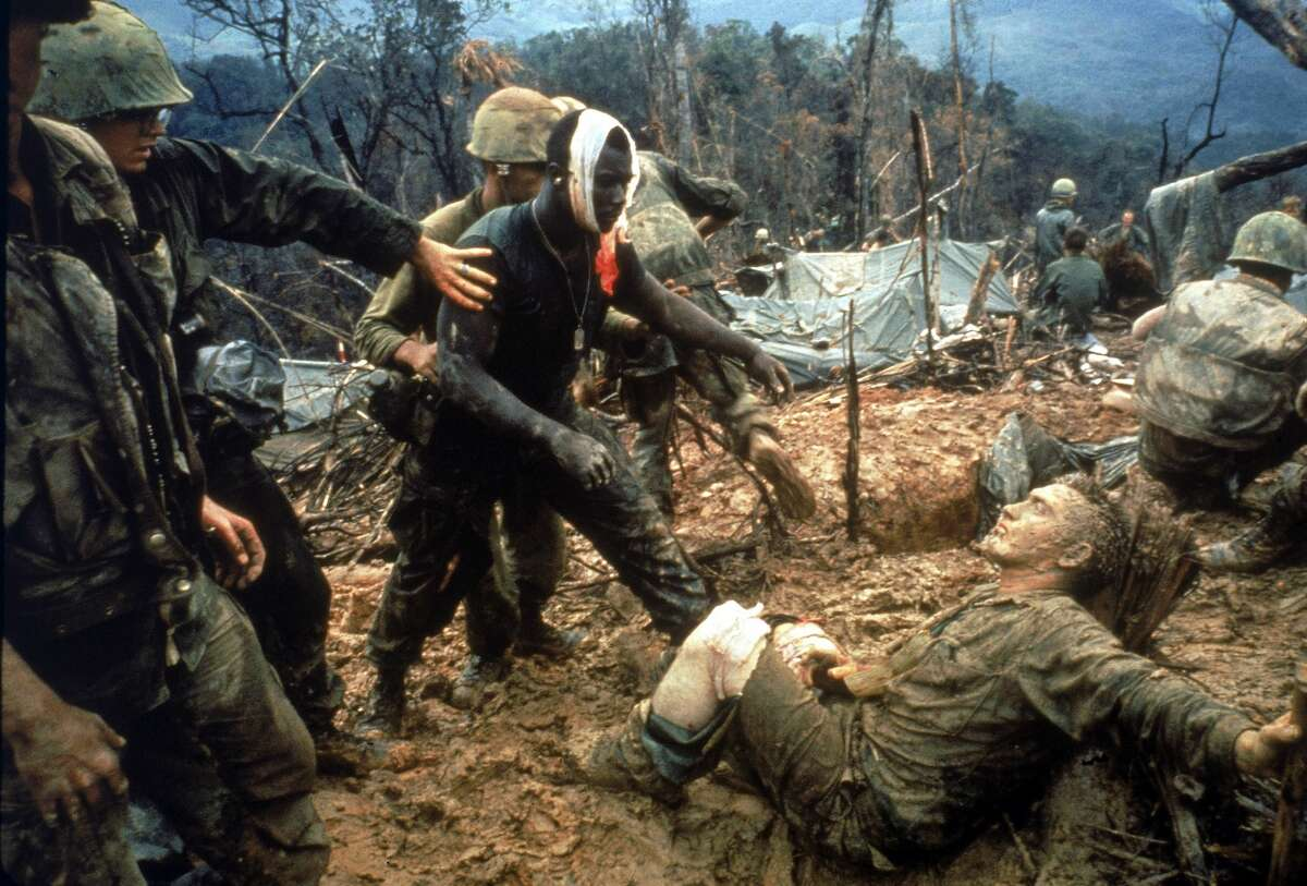 Wounded Jeremiah Purdie being led past stricken comrades circa 1966 during the fierce firefight for control of Hill 484 just south of the DMZ during the Vietnam War.