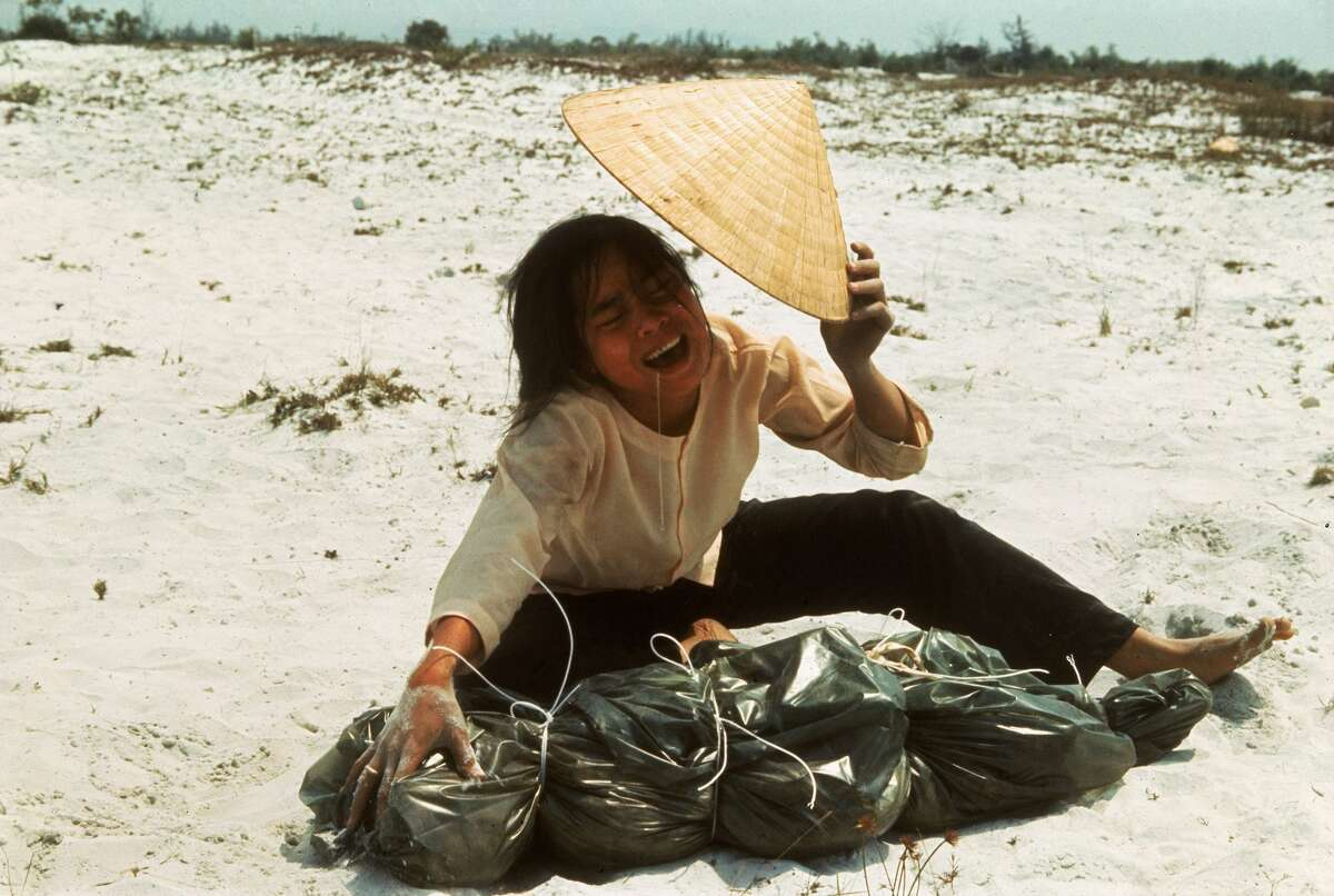 Grieving widow cries over a plastic bag containing remains of her husband in April 1969, recently found in mass grave of civilians killed by the Viet Cong during the Tet offensive, February 1968.