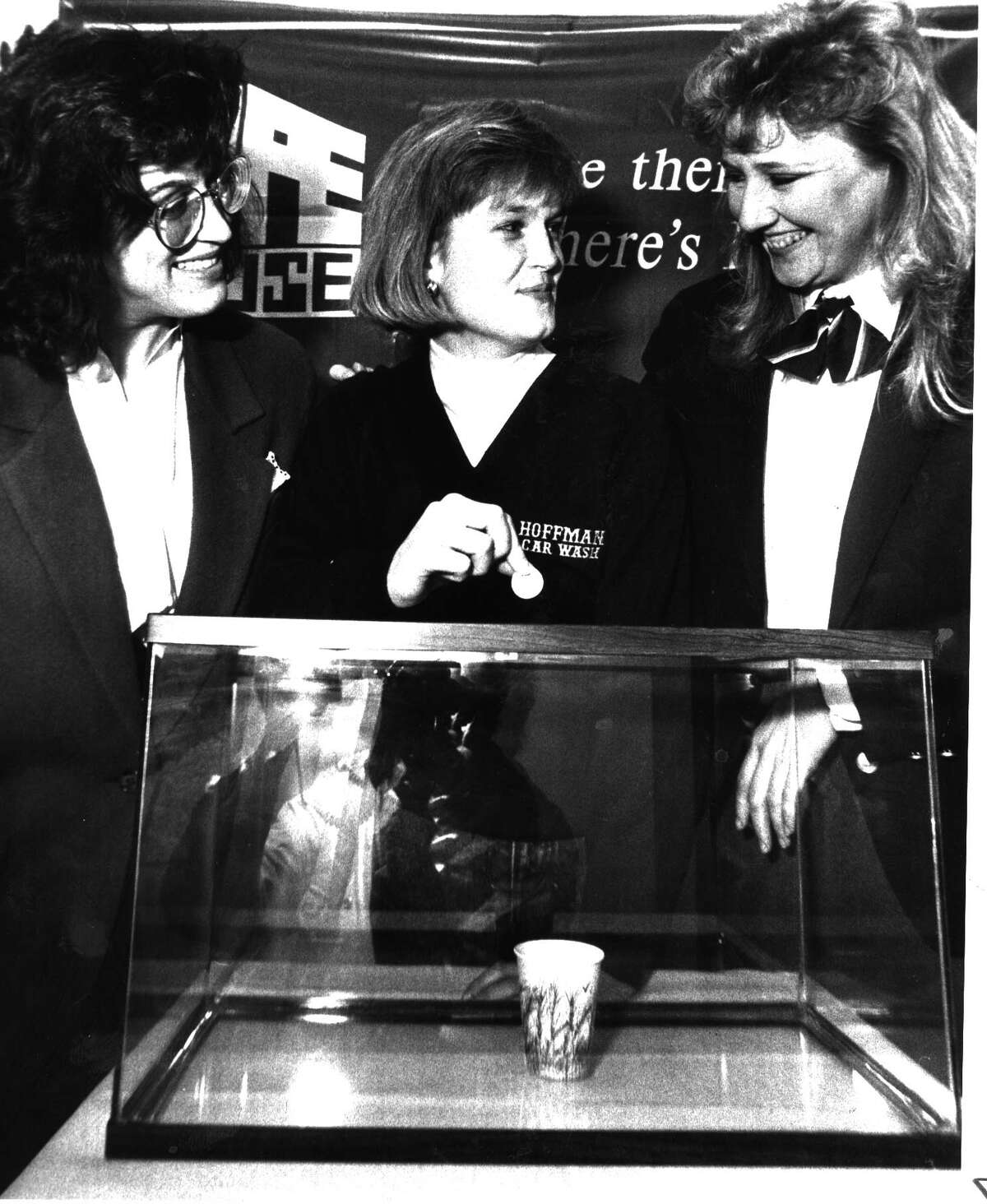 Arlene Murphy of Hope House and Carrie Hoffman of the Hoffman car wash, and Kerry Pegler assistant manager of Hoyt Theater drop a coin in cup in fish tank to win a movie pass. 3/4/1992.