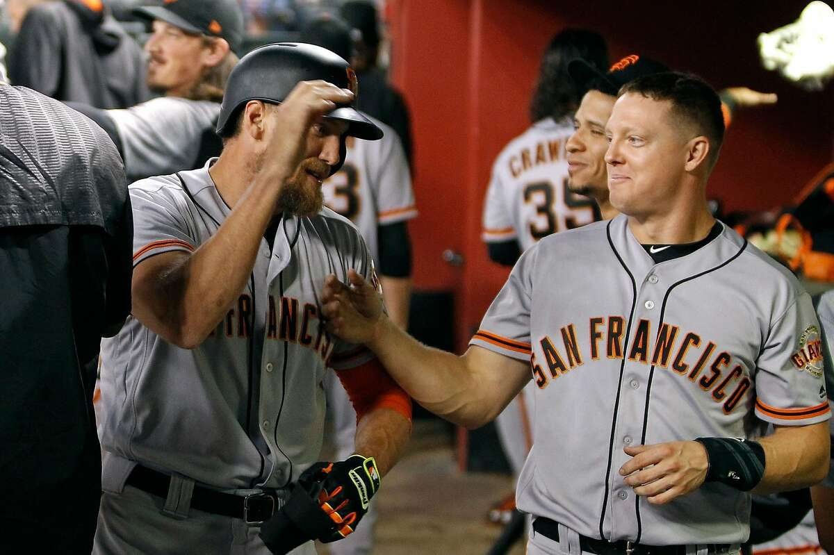 PHOENIX, AZ - SEPTEMBER 25: Hunter Pence #8 of the San Francisco Giants (L) is congratulated by teammate Nick Hundley #5 after hitting a solo home run against the Arizona Diamondbacks during the fourth inning of a MLB game at Chase Field on September 25, 2017 in Phoenix, Arizona. (Photo by Ralph Freso/Getty Images)