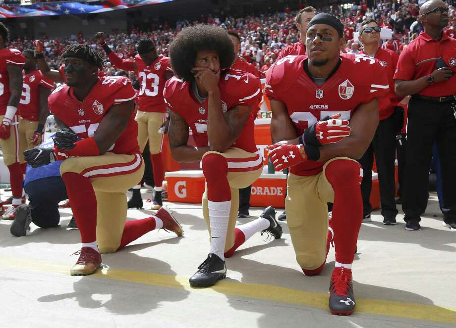 It all started with San Francisco 49er quarterback Colin Kaepernick, center. He is shown kneeling here during the national anthem last year with, from left, teammates Eli Harold and Eric Reid. Photo: Nhat V. Meyer /TNS / San Jose Mercury News