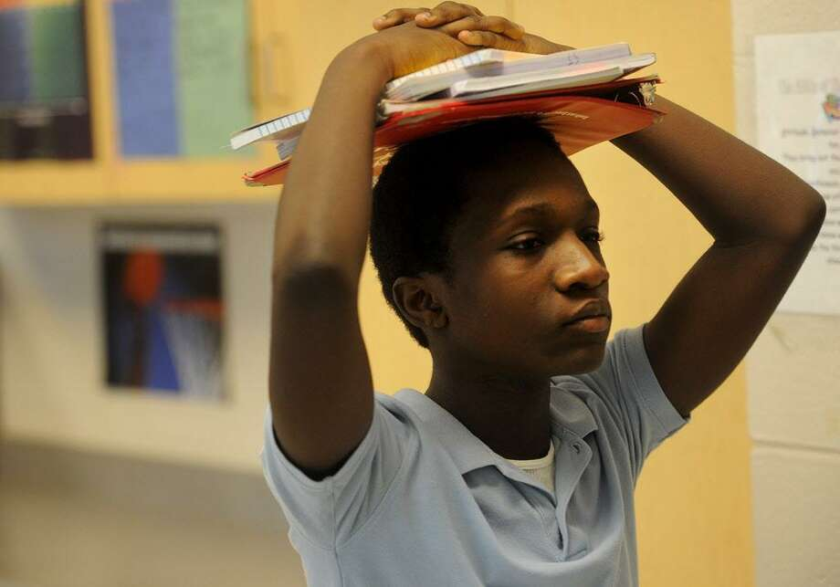 Eighth grader Lorenza Neson carries his books on his head as he leaves his Algebra class at Jettie Tisdale School in Bridgeport, Conn. on Wednesday, September 14, 2016. Eaddy's teacher Liz Capasso testified in the CCJEF trial which resulted in a recent judge's ruling demanding sweeping changes to school funding. Photo: Brian A. Pounds / Hearst Connecticut Media / Connecticut Post