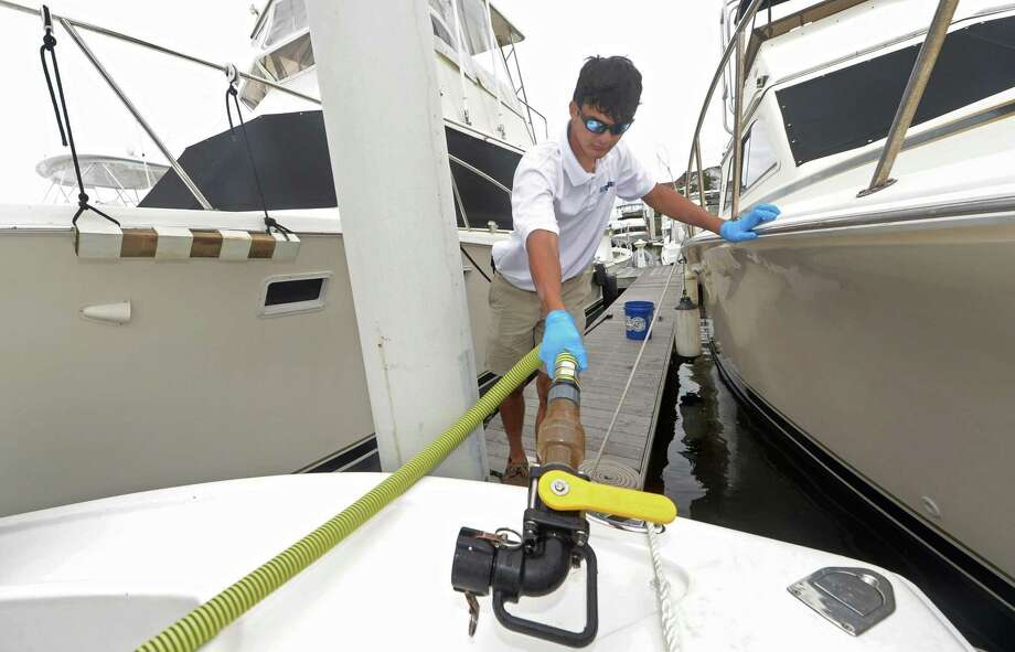 East Norwalk Blue employee Andrew Nanai pumps sewage from recreational boats in Norwalk Harbor Tuesday, August 8, 2017,  in Norwalk, Conn. The nonprofit company inherited a fleet of pump out boats from the previous Sound Keeper and visits boaters who need to empty their holding tanks and then transfers the sewage to the Norwalk's septic system, keeping it out of the Harbor and Long Island Sound. The state sponsored program is offered free to boat owners and since it started earlier this year East Norwalk Blue has completed over 1000 pump outs to recreational vessels in the Western sound. Photo: Erik Trautmann / Hearst Connecticut Media / Norwalk Hour