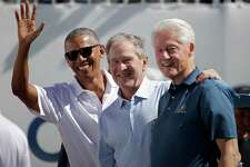 Former U.S. Presidents, from left, Barack Obama, George Bush and Bill Clinton greet spectators on the first tee before the first round of the Presidents Cup at Liberty National Golf Club in Jersey City, N.J., Thursday, Sept. 28, 2017. (AP Photo/Julio Cortez)